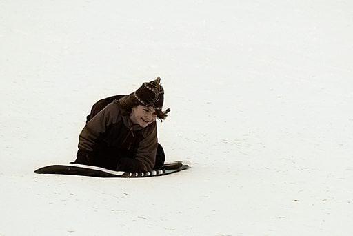 young boy sledding over snow