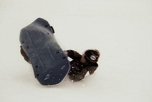 young boy enjoys sledding over snow