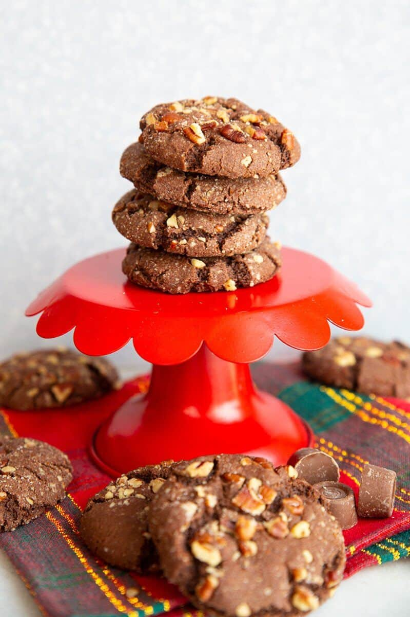 stack of Rolo Cookies on a red cake stand and all over the table