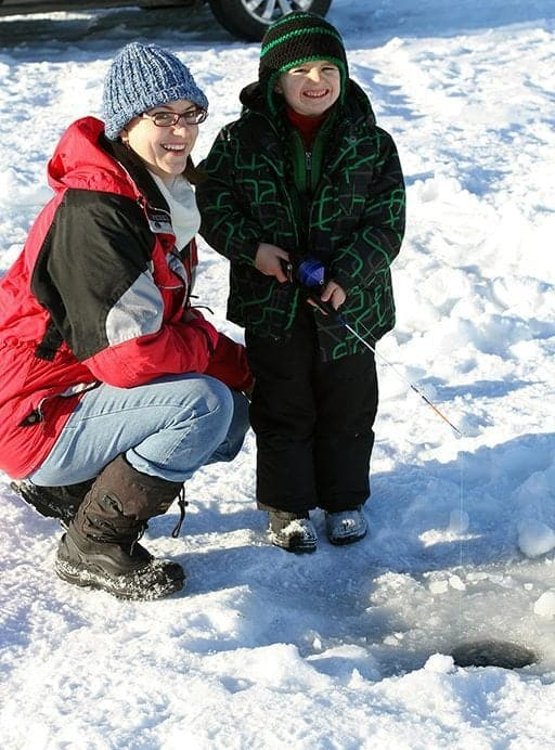 Mom and her kid doing an ice fishing