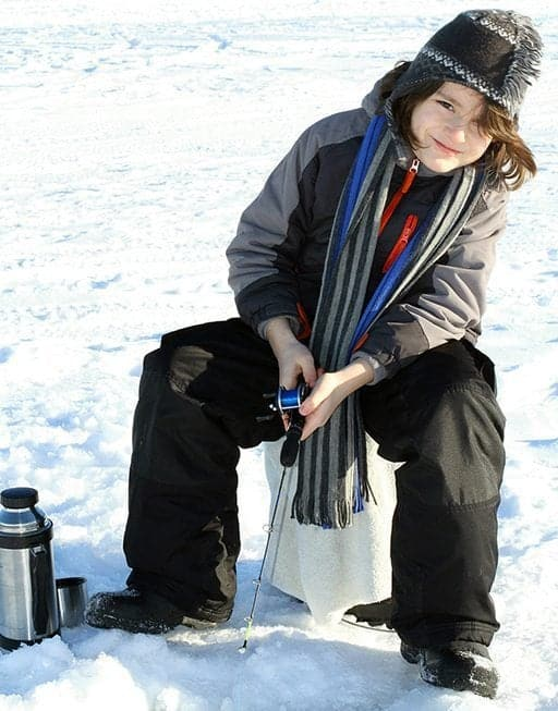 young boy sitting while his fishing rod on the hole for fishing