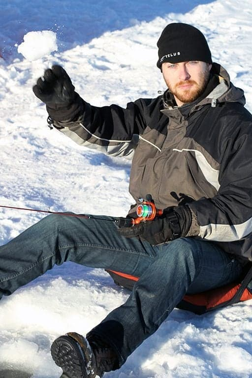 man sitting the ice throwing some snowballs up while holding the fishing rod