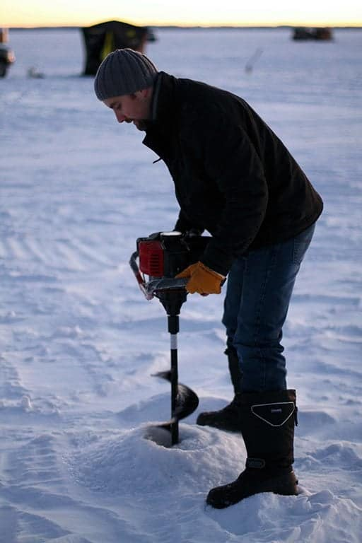 man creating hole for ice fishing