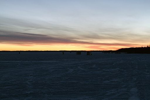 view of sunrise from a lake full of ice