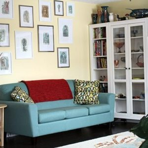 wall with framed art works, retro color couch and white shelving