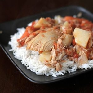 Chicken & Potato Stew on top of rice in a black plate bowl