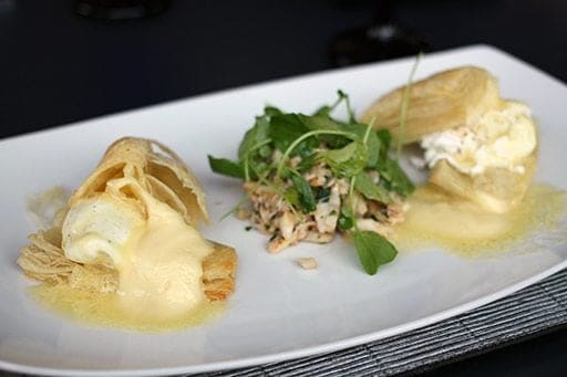 white rectangular plate with mimosa's and crab Eggs Benedict with Hollandaise