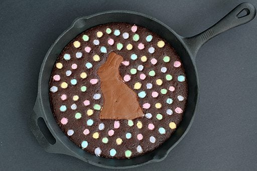 top down shot of Skillet Brownie with a chocolate bunny smack dab in the middle, surrounded by colored M&M's