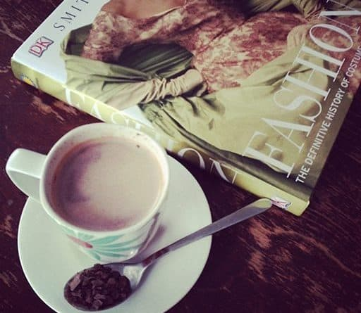 top down shot of a cup of coffee beside a fashion book