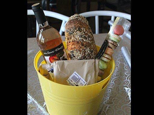 big yellow bucket with En Sante's Rhubarb wine, Duchess macarons, a gift package, Sylvan Cheese's Old Grizzly and a loaf of pumpkin sourdough