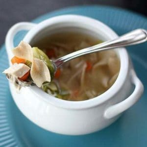 Cheater Chicken Soup in a white bowl with handle, a spoon with vegetables and chopped chicken on top of the bowl