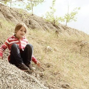 young girl enjoys sliding down dusty hill