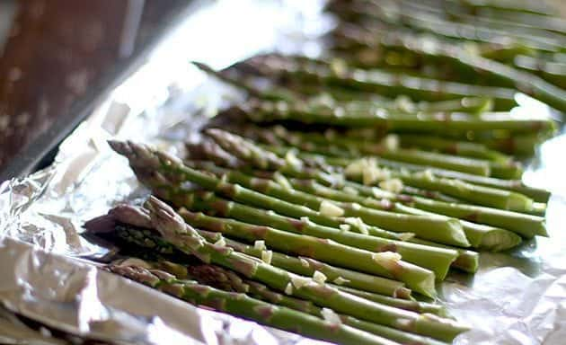 asparagus in a foil lined baking sheet sprinkled with garlic