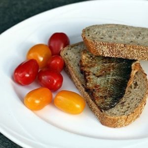 whitefish fillets, slices of bread and fresh small tomatoes in a white plate