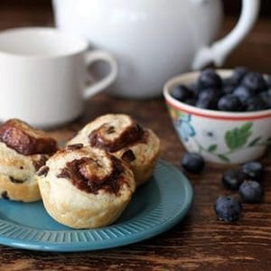 Three Pieces Philly Chocolate Cream Cheese Breakfast Biscuits in a Blue Plate and a Bowl of Fresh Blueberries