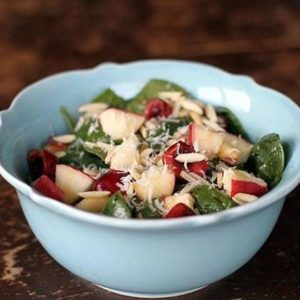 Close up of Apples N' Cherries Spinach Salad in a blue Pyrex bowl
