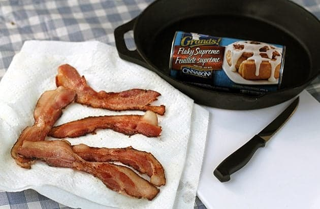 five slices of cooked bacon in a paper towel, a can of Pillsbury Grands! Cinnamon rollss in a skillet and a knife