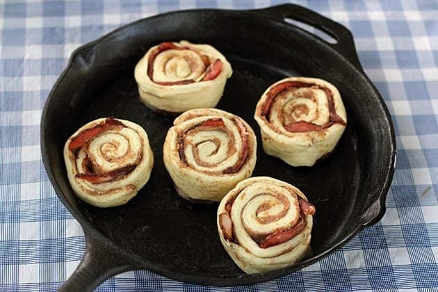 rolled back cinnamon buns with bacon in a skillet