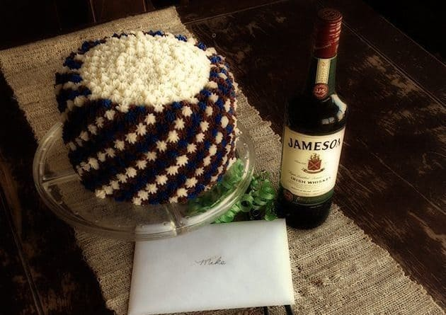 Simple Father's Day Cake with white and brown star icing, a bottle of whisky beside it