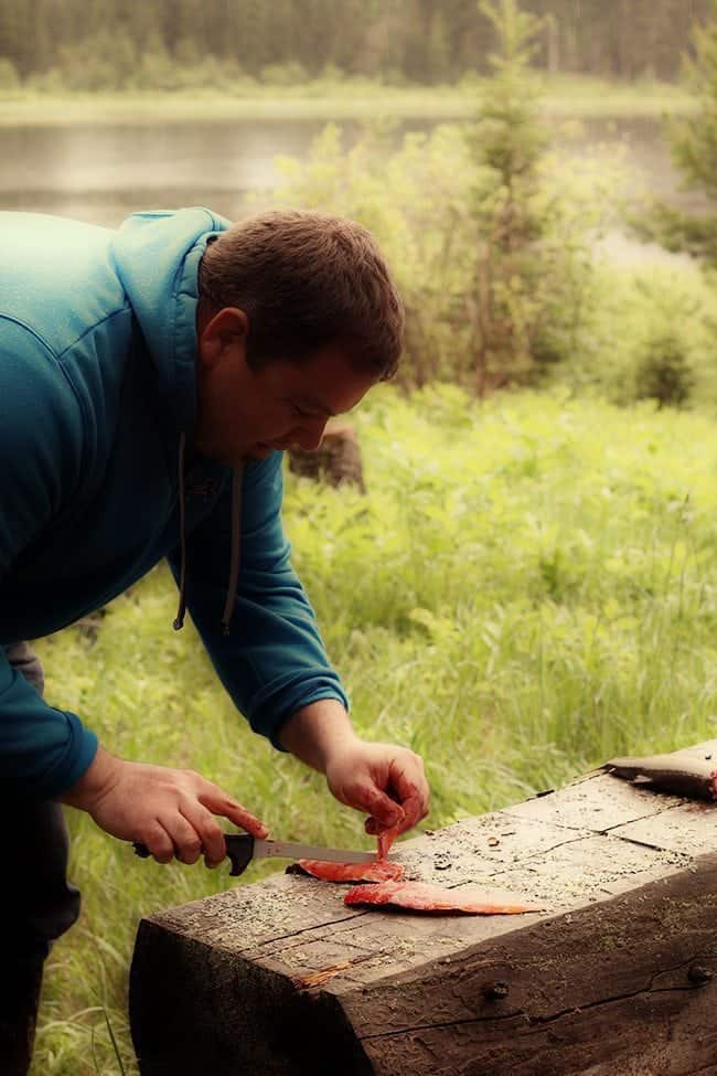 man slicing the brook trout
