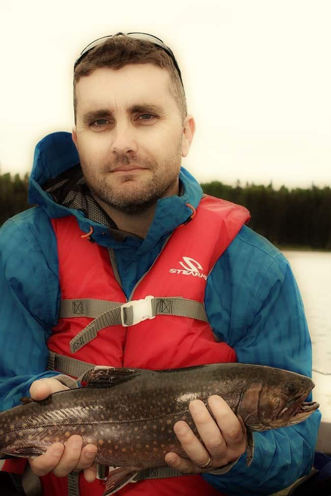 man holding brook trout with red and blue spots