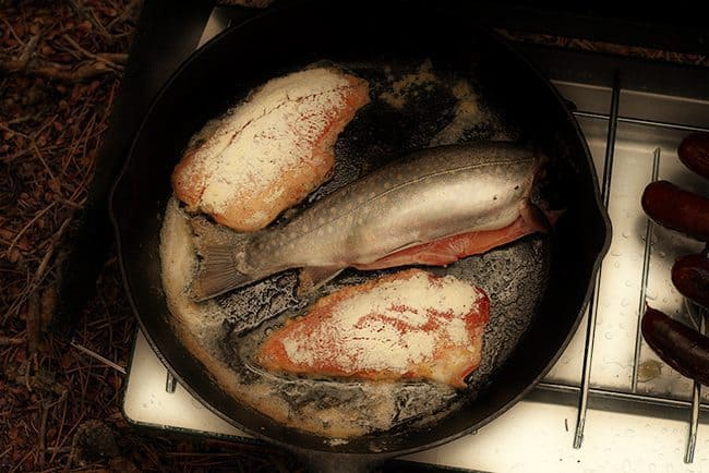 cleaned and sliced brook trout in skillet with butter