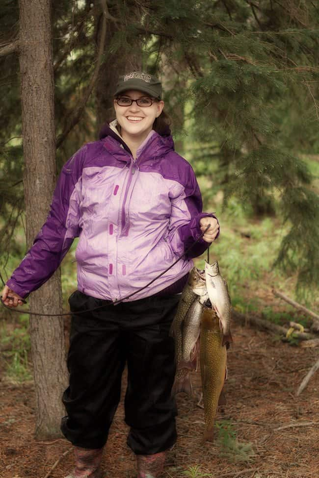 woman in violet jacket holding a string with all caught brook trout