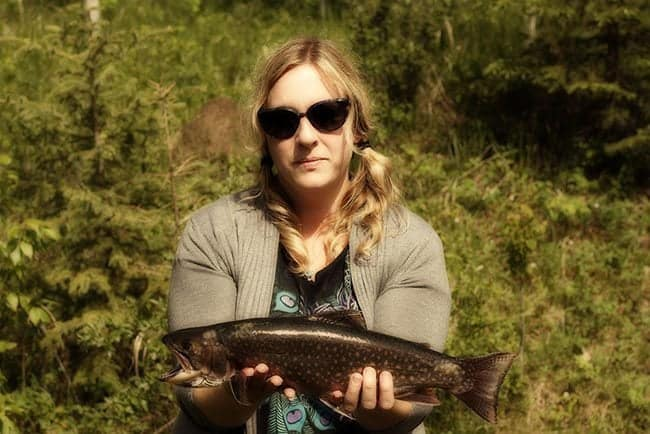 woman in sun glasses holding a brook trout fish