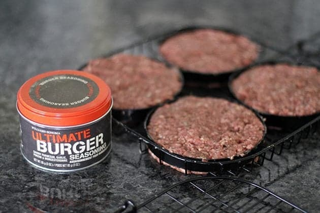 a can of Ultimate Burger Spice and burger patties in william's sonoma hamburger grilling basket