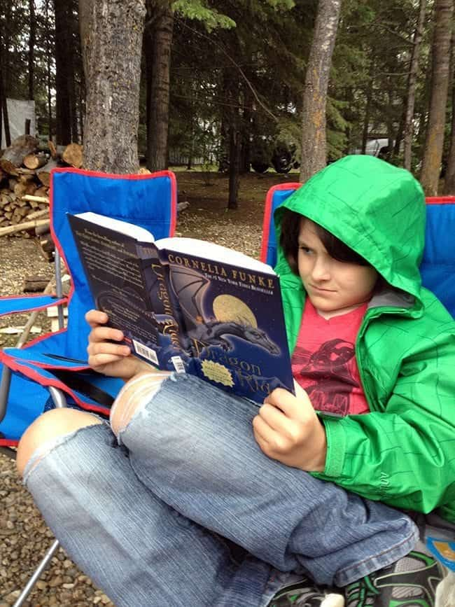 young boy reading a book while sitting in a camping chair