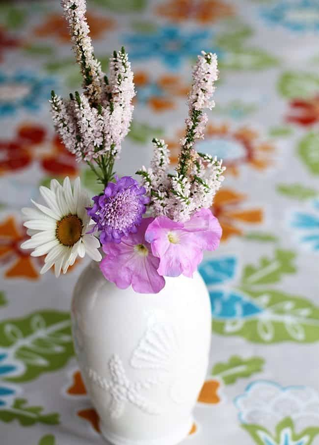 variety of flowers in a white sea shell vase