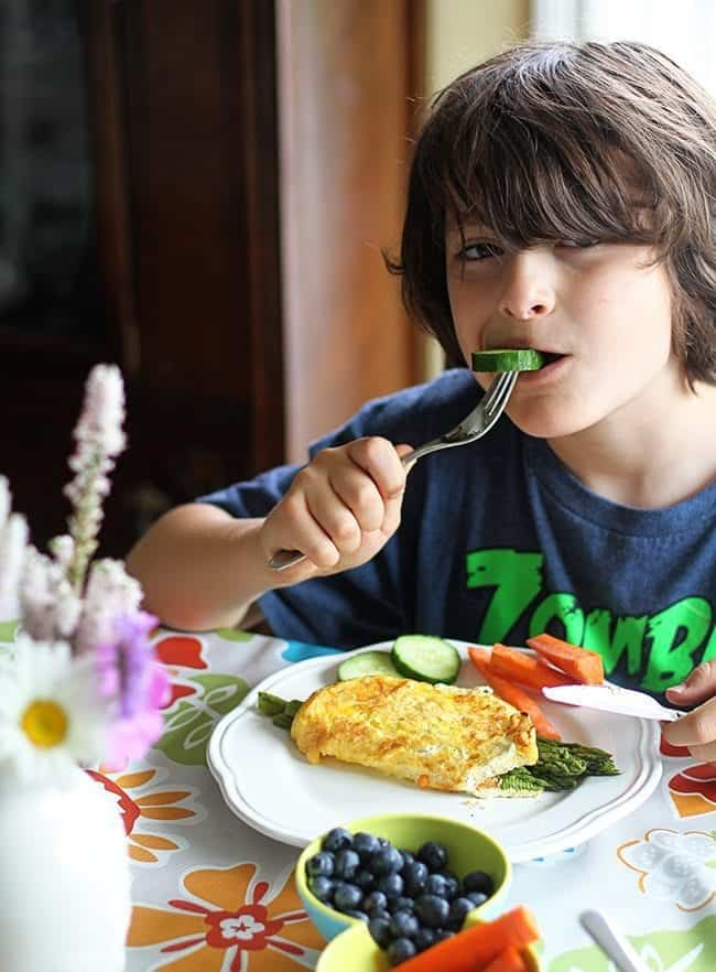 young boy having a bite of fresh cucumber slice in his fork