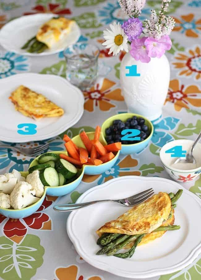 plates with asparagus and cheese omelettes, serving dishes with vegetables and blueberries on the table