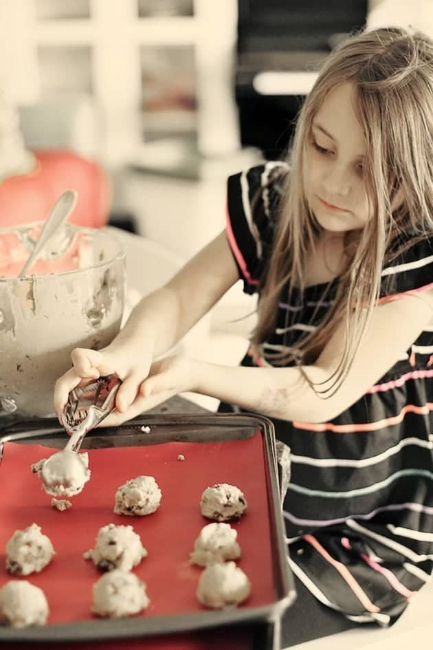 little girl uses a cookie scoop to shape the Raisin Molasses Gems