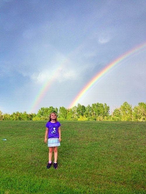 young girl in blue shirt and skirt standing in the field with rainbow on background