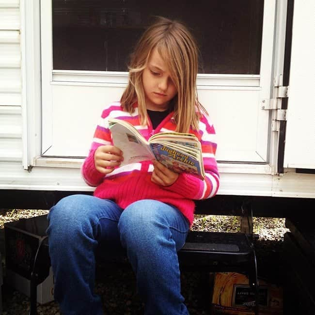 young girl reading a book while sitting near the white door