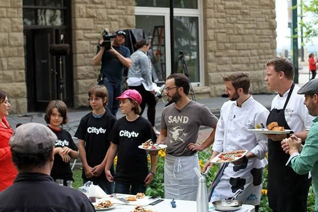 kids and chefs all lined up with plates in their hand to hear a winner
