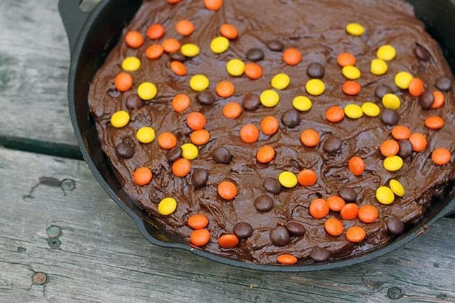 Reese's Pieces sprinkled on top of the brownie mix in the skillet