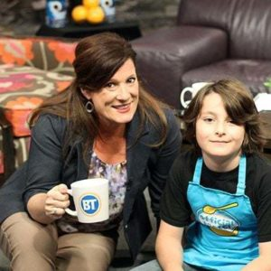 breakfastTV host holding a mug and a young boy wearing kitchen apron