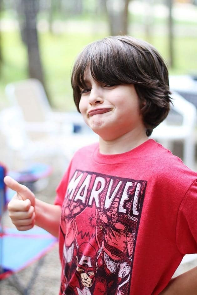 young boy wearing red shirt in his goofy face