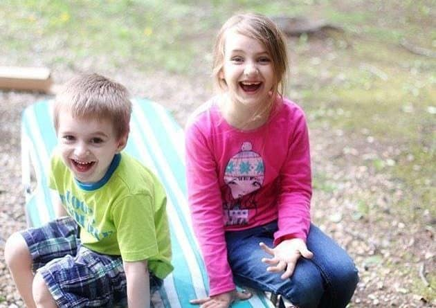 little boy and girl sitting and making goofy face