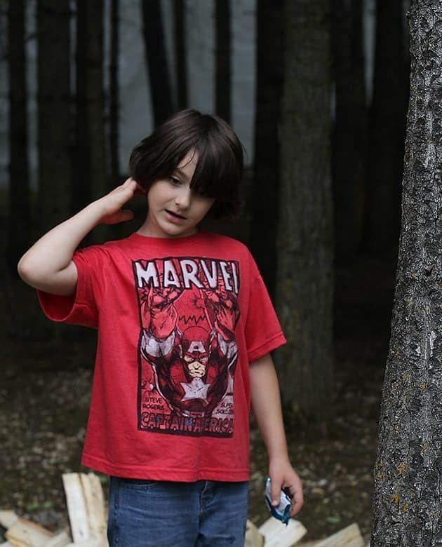 young boy in woods scratching the back of his head