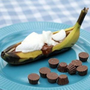 Close up of Reese's Peanut Butter Cup Banana Boat in blue plate