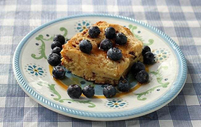 close up of Baked French Toast with maple syrup and fresh blueberries in small dessert plate