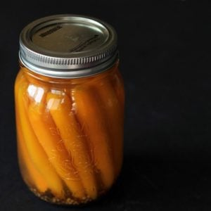 close up of sweet Pickled Carrots in a canning jar with pickling liquid in a dark background