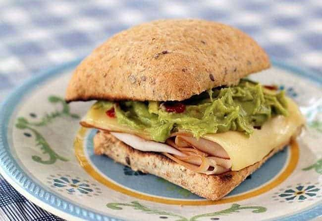 toasted buns with turkey at the bottom, top with Swiss cheese, guacamole and mastard