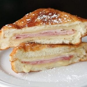 close up sliced Disneyland Monte Cristo Sandwiches with icing sugar in a white plate