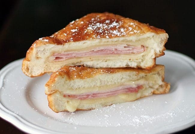 sliced Disneyland Monte Cristo Sandwiches with icing sugar in a white plate