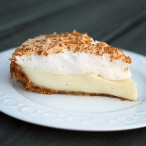A slice of Flapper Pie in a White Plate with cinnamon laced graham crumbs on top