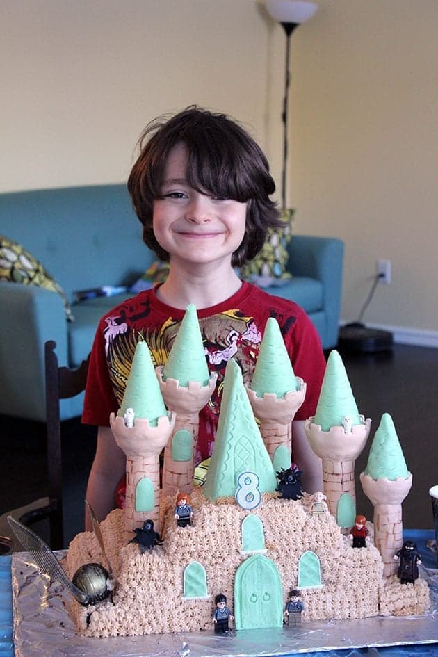 Hogwarts cake in front of a boy wearing red shirt